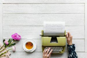 Imagem de mãos de jovem mulher utilizando uma máquina de escrever