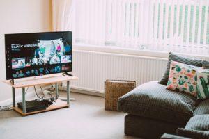 Imagem de um sofá e de uma televisão ligada em um programa animado