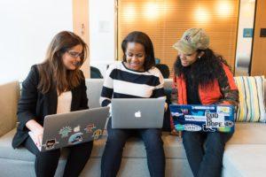 Imagem de 3 moças em um sofá com laptops no colo