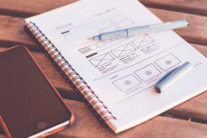 Imagem de um caderno com ilustrações de quadrinhos e legendas em uma das páginas e um smartphone ao lado