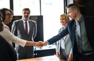Imagem de uma equipe de colegas de trabalho apertando as mãos