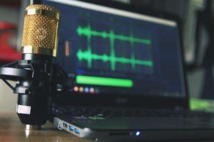 Imagem de um microfone profissional em frente a um laptop