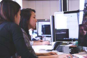 Imagem de duas mulheres olhando para o computador.
