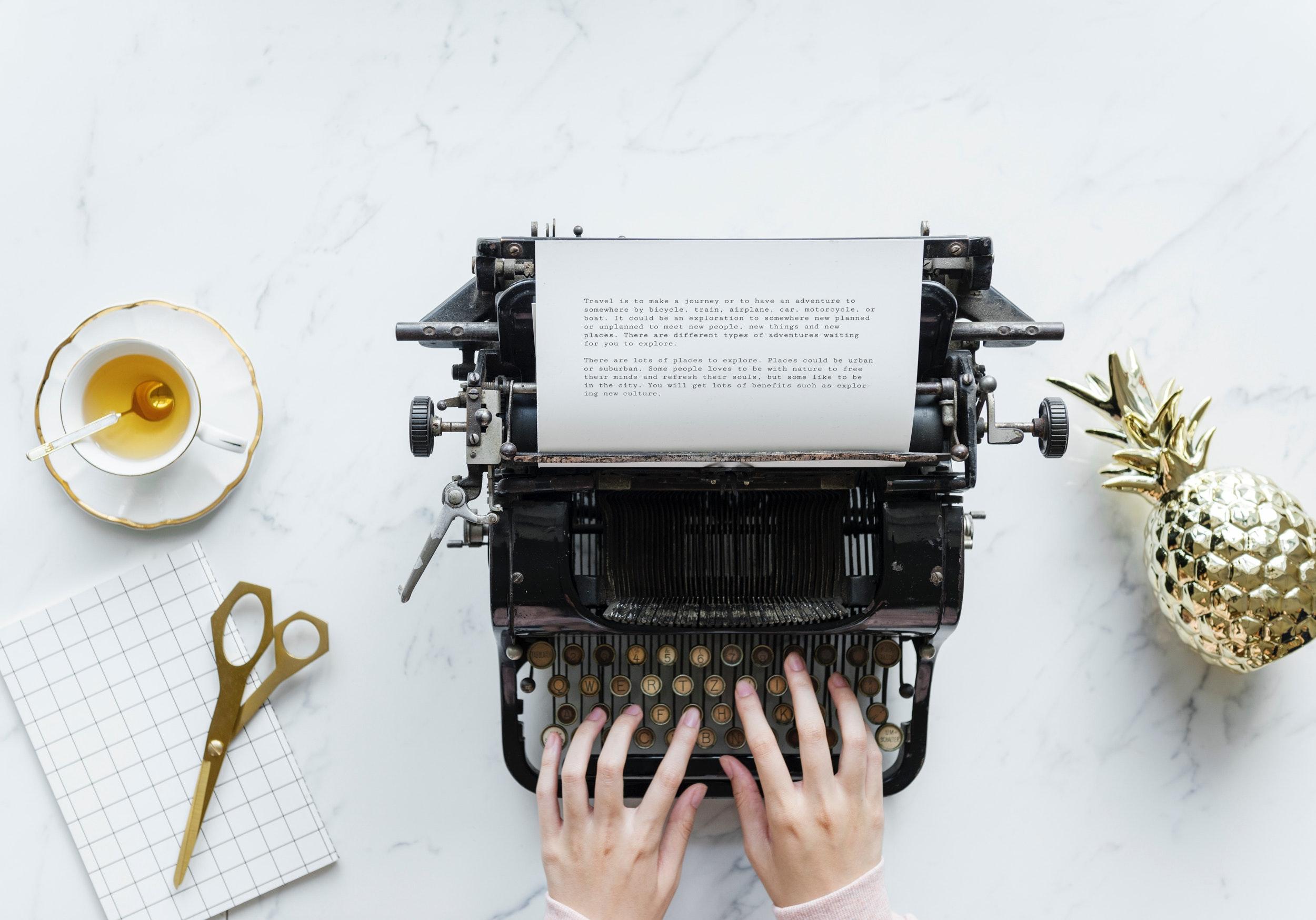 Imagem de mãos teclando na Máquina de Escrever e um chá ao lado