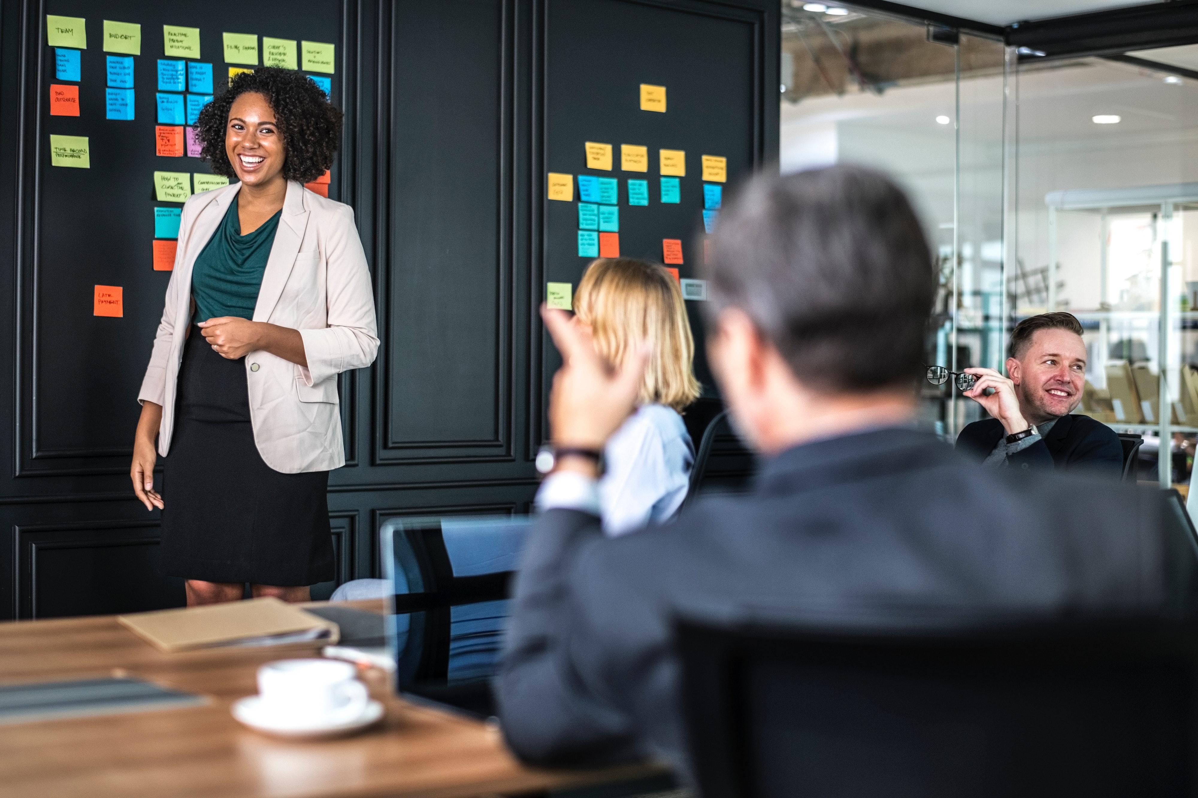 Imagem de 4 pessoas sorrindo em uma sala de reuniões