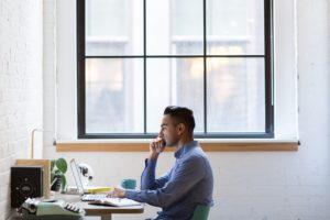 Imagem de um jovem rapaz sentado em frente à sua mesa de trabalho